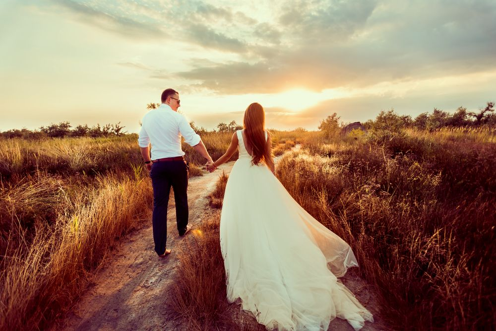 Back view of romantic couple of bride and groom walking hand in hand on rural road at sunset
